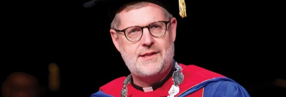 The Rev. Dennis H. Holtschneider, C.M., president of DePaul University address the audience during the College of Law commencement May 18, 2014 at the Rosemont Theatre in Rosemont, IL. Some 313 students earned law degrees — 295 Juris Doctors and 18 Master of Laws degrees, in health law, intellectual property, international law and taxation. (DePaul University/Jeff Carrion)
